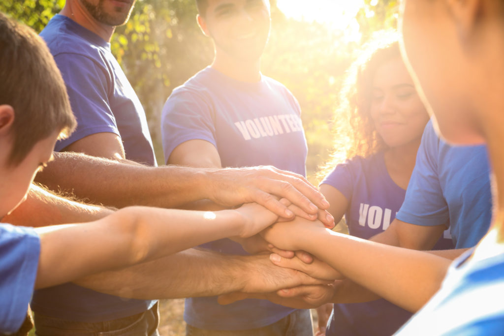 Group of volunteers joining hands together outdoors on sunny day